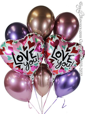 Love you balloon bouquet with six chrome purple mauve and rose gold latex balloons and two heart shaped foil balloons printed with red pink and turquoise mini hearts and a printed Love You! message.